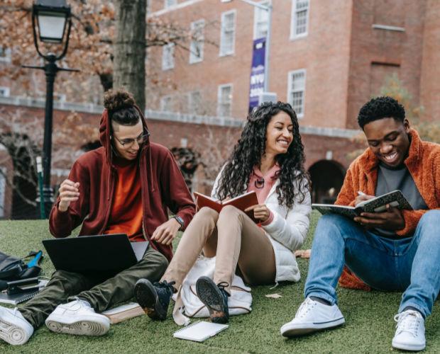 cheerful multiethnic students with books sitting near university