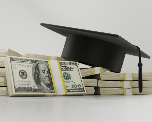 graduation cap on stacks of dollar bills